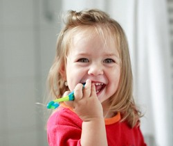 little girl in red shirt holding toothbrush