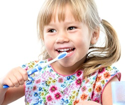 little girl with pigtails brushing teeth