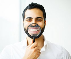 man using magnifying glass to show off results of teeth whitening in Coppell