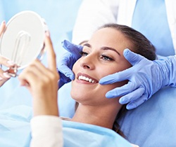 woman sitting in dental chair and smiling at hand mirror