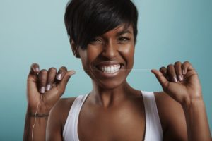 Woman smiles while flossing as recommended by her Coppell dentist